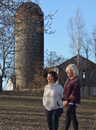 Val Crowley (left) and Marie Adamcryck, authors of Silos, Stories and Sketches of Otonabee-South Monaghan Township, in front of one of the silos featured in the book. PAT MARCHEN/Special to Peterborough Examiner